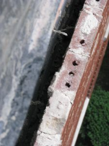 Figure 2. Cavity brick face collapse. The corroded tie does not engage the face brick anymore.