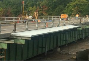 Figure 2. New gray W-8 I-beams bolted on top of the original green W-40 beams demonstrate the lightweight FRP product's design flexibility to increase clear sidewalk width and support modern traffic requirements.