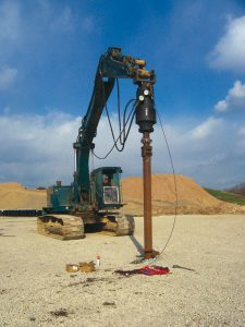 Crane operators begin installing a helical pile shaft into the site's foundation. Soil type and a pile's size and shape factor into installation resistance.