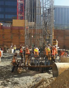 Workers splice together two sections of reinforcing steel that form drilled piers used in the foundation for 1144 Fifteenth Street.