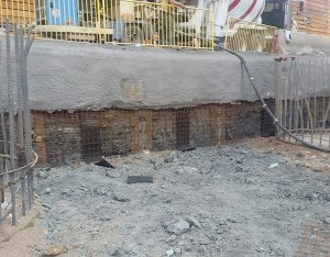 Drilled piers on either side of the excavated bedrock with the first phase of shotcrete applied.
