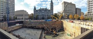 Taken from the pediatric care building, excavation, and SOE at the start of mat foundation construction. Historic Old City Hall is in the background. Courtesy of Skanska USA.