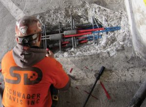 Figure 1. Worker repairs parking garage slab PT strand with couplers.