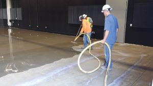 Figure 6. Installation of a cement underlayment in which the thinness of the application can be observed. Prior to installation, the concrete subfloor had to be shot blast to ensure adequate bonding of the underlayment.