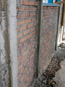 Installation of the mesh plaster overlay during pilot construction.