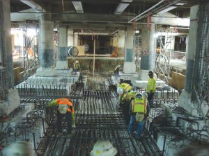 """Figure 4. Crews install foundation reinforcement at the bottom of the new mat foundation. Notice """"wedding-cake"""" style original concrete foundations at varying elevations."""